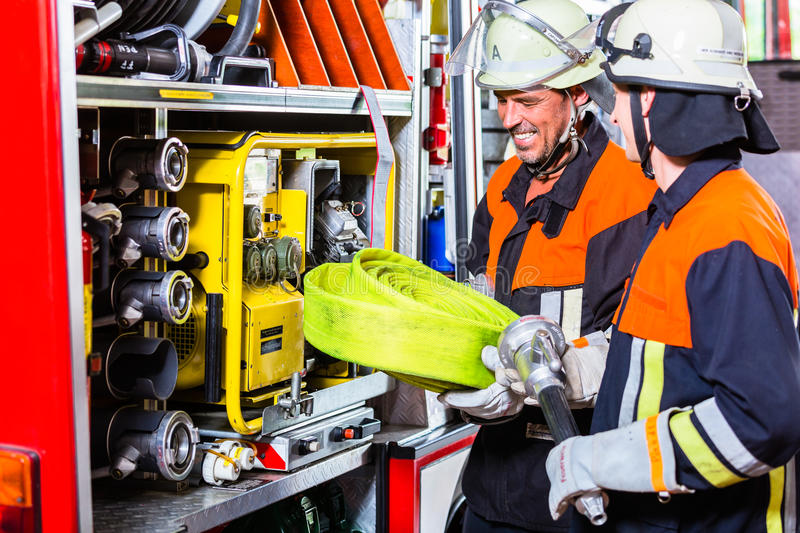 Fire fighters loading hoses into operations vehicle. Female fire fighters loading hoses into fire engine stock images