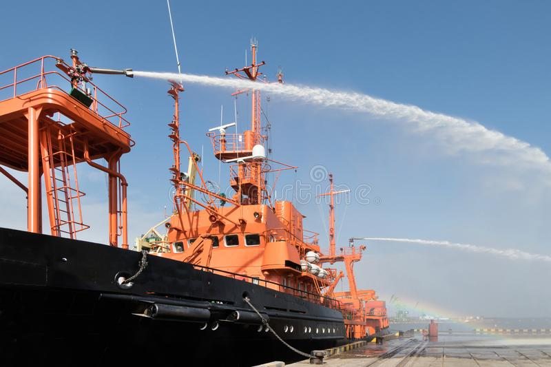 Fire fighting boat sprays water in port.The fire ship is testing the fire fighting equipment in the port royalty free stock photography