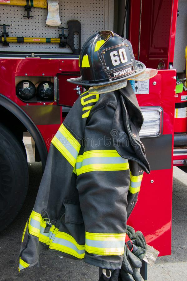 Fire fighting gear including helmets and jackets were displayed near a fire truck display at the Princeton Arts Festival. Princeton, New Jersey - April 28, 2019 royalty free stock image