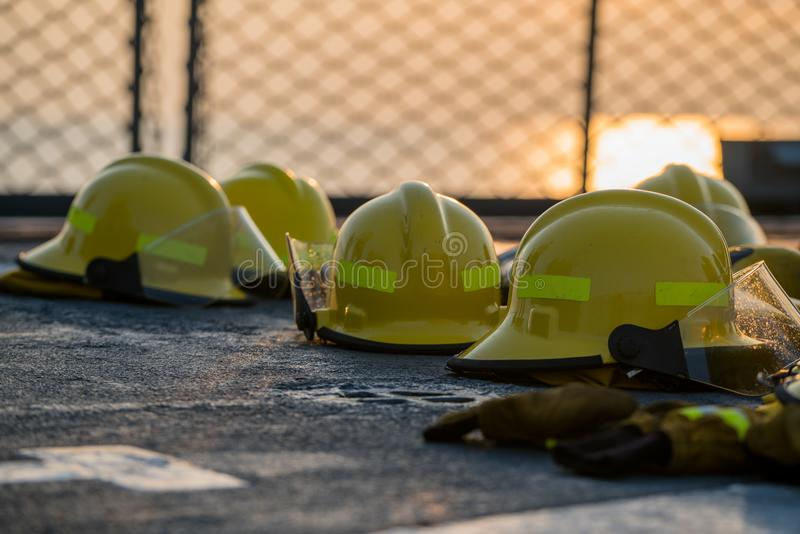Fire fighting helmets are drying on the navy ship deck after use. Safety net has seen as a background. orange sky between sunset p stock image