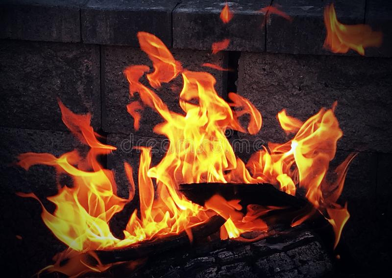 Fire in a fire pit. A swaying yellow and orange fire on dark logs in the night stock photos