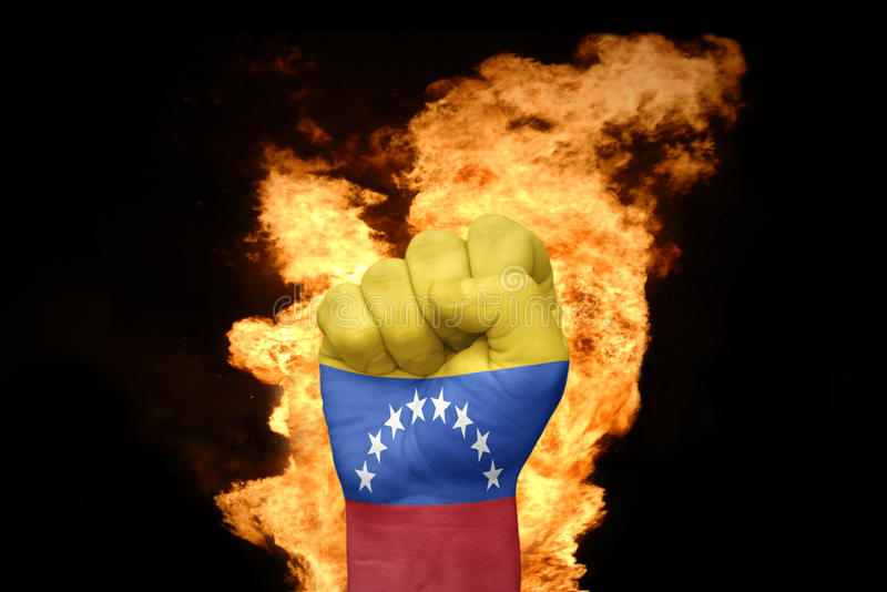 Fire fist with the national flag of venezuela stock image