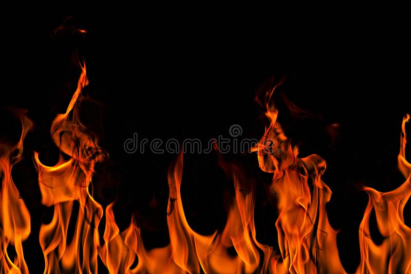 Fire flames on Abstract art black background, Burning red hot sparks rise. Fiery orange glowing flying particles royalty free stock photos