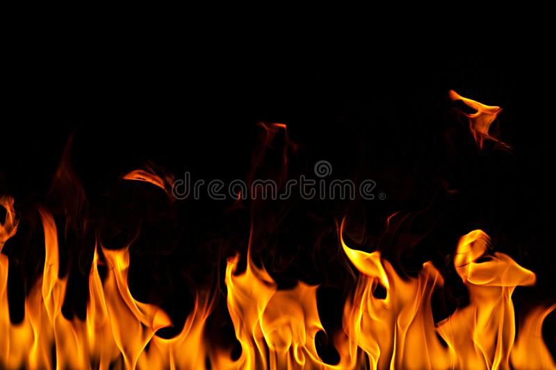 Fire flames on Abstract art black background, Burning red hot sparks rise. Fiery orange glowing flying particles stock images