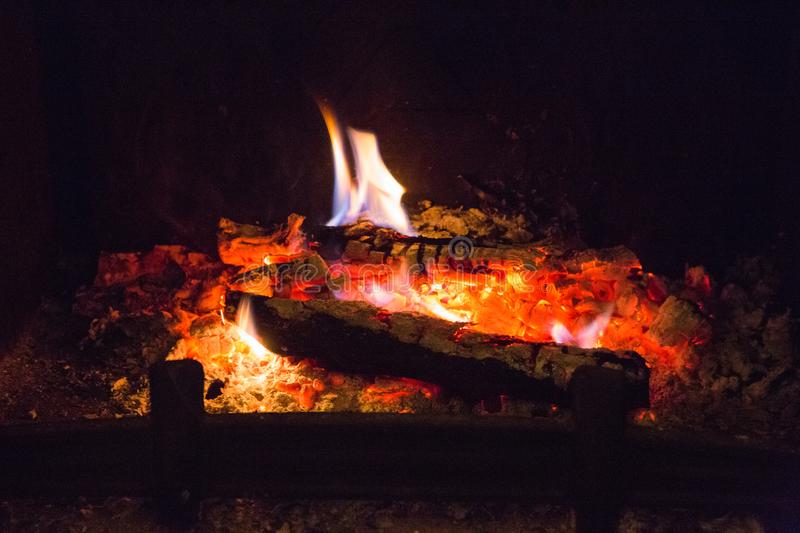 Fire flames with ash in fireplace stock image