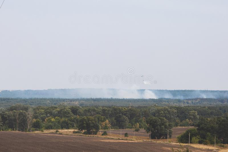 Fire in forest. Helicopter dpirs and drops water in epicenter of incident.  stock photo