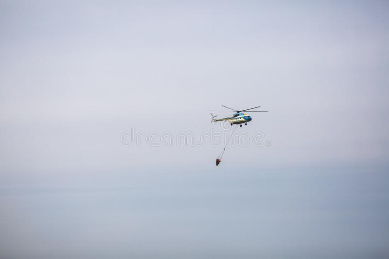 Fire in forest. Helicopter dpirs and drops water in epicenter of incident.  stock photos