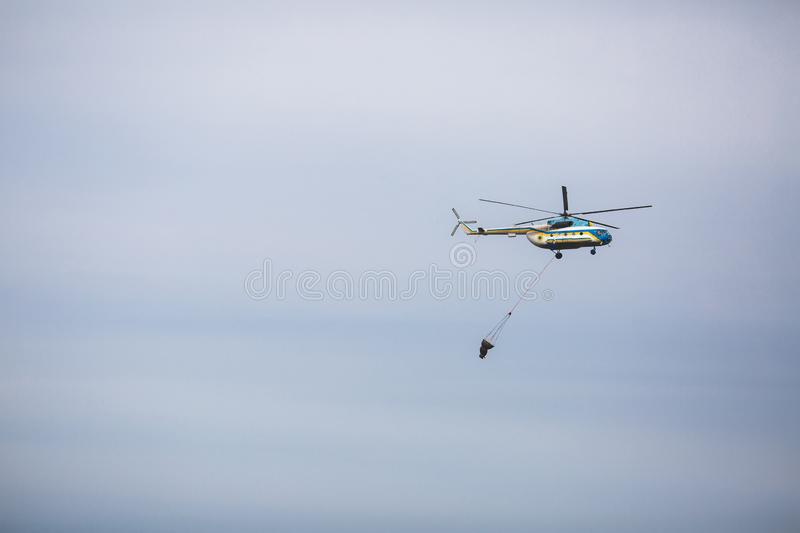 Fire in forest. Helicopter dpirs and drops water in epicenter of incident.  royalty free stock photography