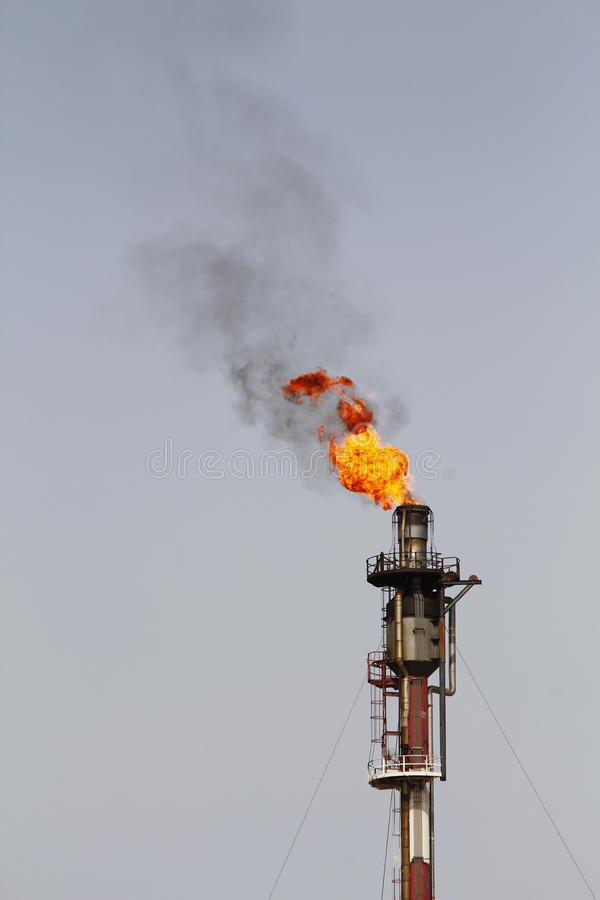 Fire from a gas torch, in a large oil refinery stock images