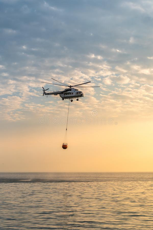 A fire helicopter collects water into the sea and flies toward the mountains to extinguish a forest fire on the royalty free stock image