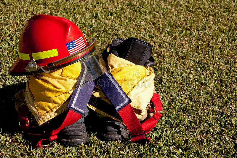 Fire Helmet and Boots. Firefighters gear sitting on grass stock images