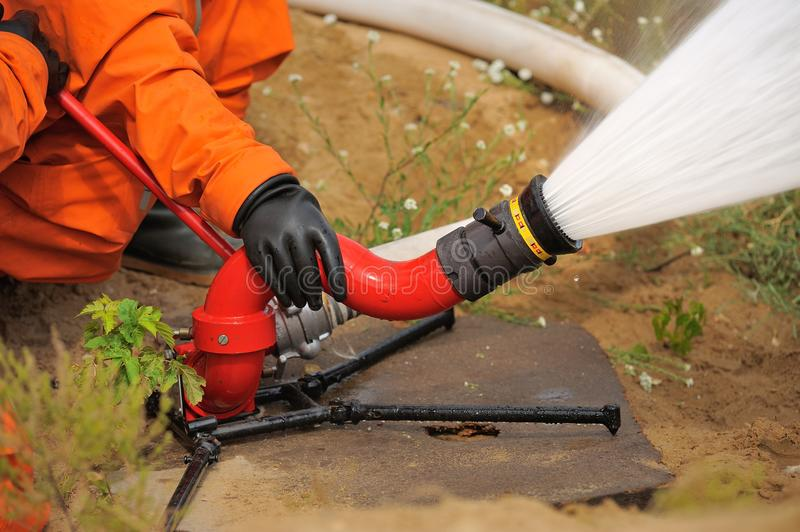 Fire hose in actions pouring water operated by fireman in orange. Uniform closeup royalty free stock photography