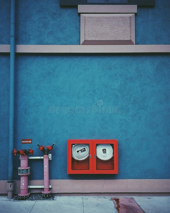 Fire hose on grunge turquoise cement wall stock photography