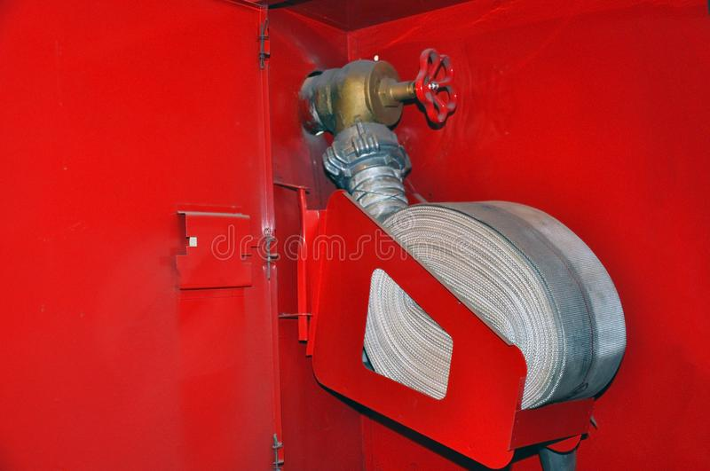 Fire hose in a twisted state in a fire shield. Fire safety royalty free stock photos