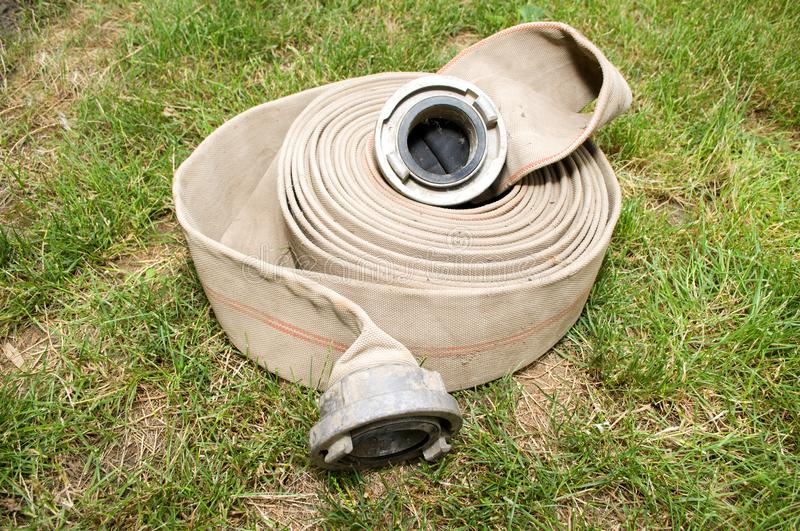 Fire hose for water. On grass stock photo