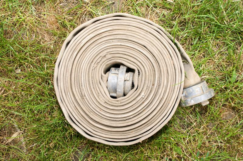 Fire hose for water. On grass stock image