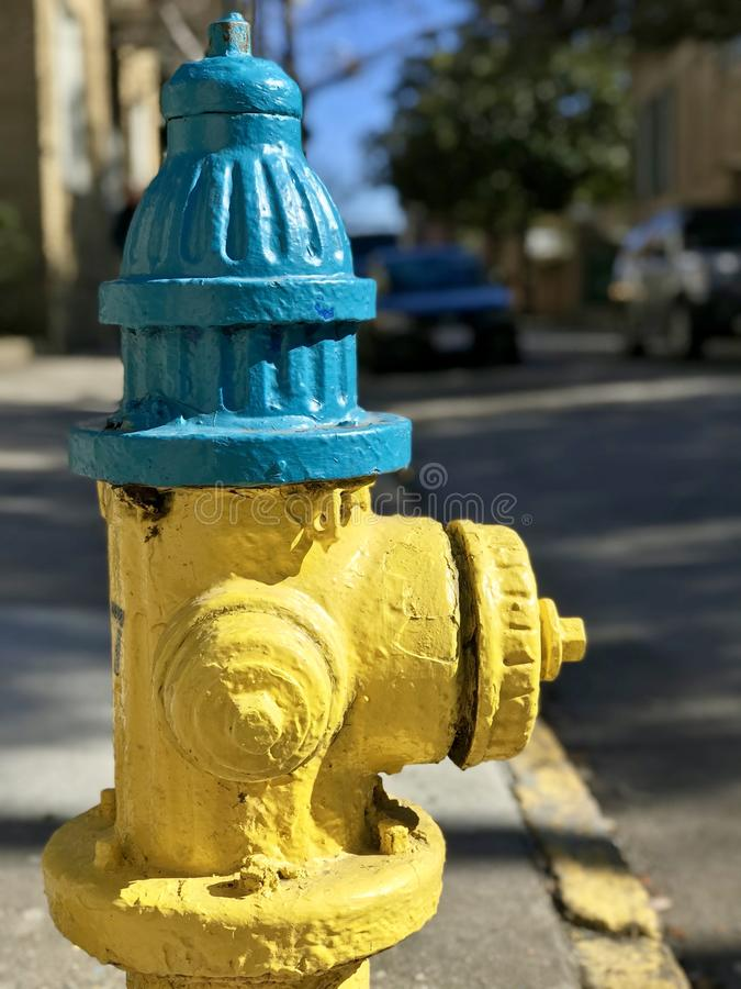 A fire hydrant is painted in blue and gold and sits in the sun - FIRE HYDRANT. A fire hydrant, also called a fireplug, fire pump, johnny pump, or simply pump, is stock photography