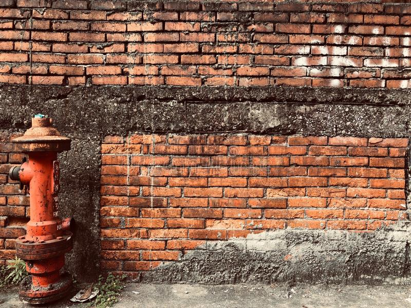 Fire hydrant in front of red brick wall royalty free stock photography