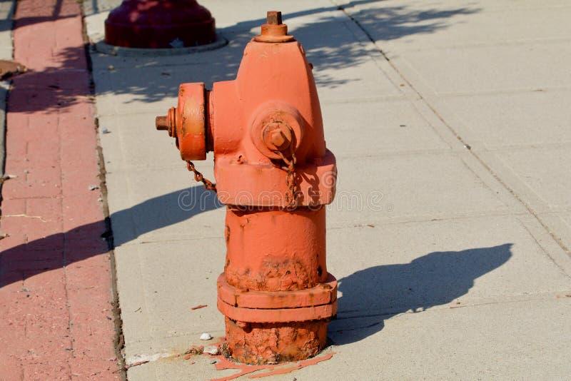 Fire hydrant. Orange fire hydrant in the bright midday sun stock photo