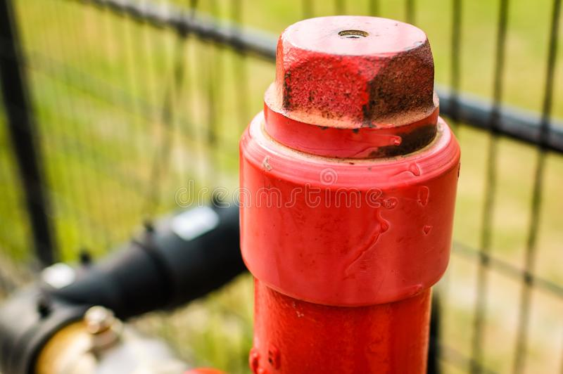 Fire Hydrant Red Top Close Detail With Soft Focus Background. A fireplug, fire pump, johnny pump, or simply pump, is a connection point by which firefighters can royalty free stock photos