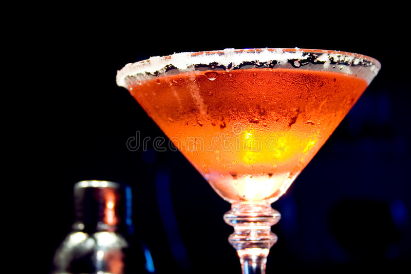 Fire and Ice Drink. Chilled martini glass trimmed with sugar and filled with an orange and red cocktail. Stainless steel shaker in the background stock photo