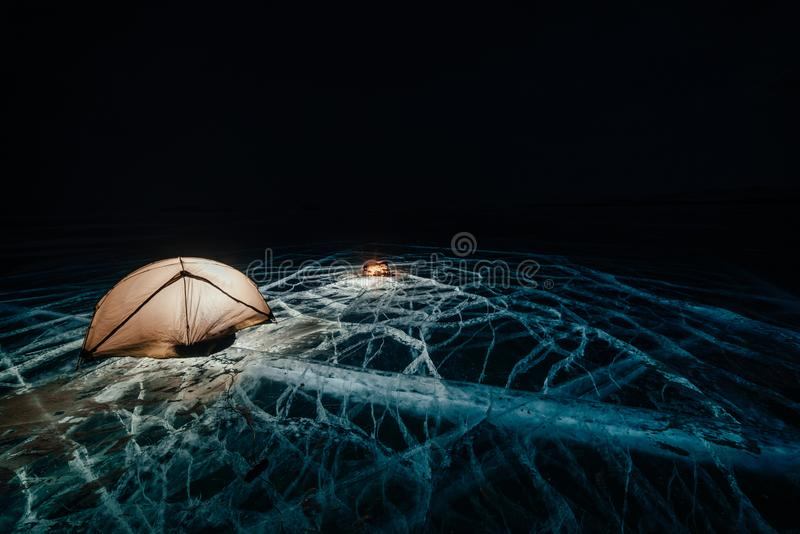 Fire on ice at night. Campground on ice. Tent stands next to bonfire. Lake Baikal. Nearby there is car. Shelter tent and stock image