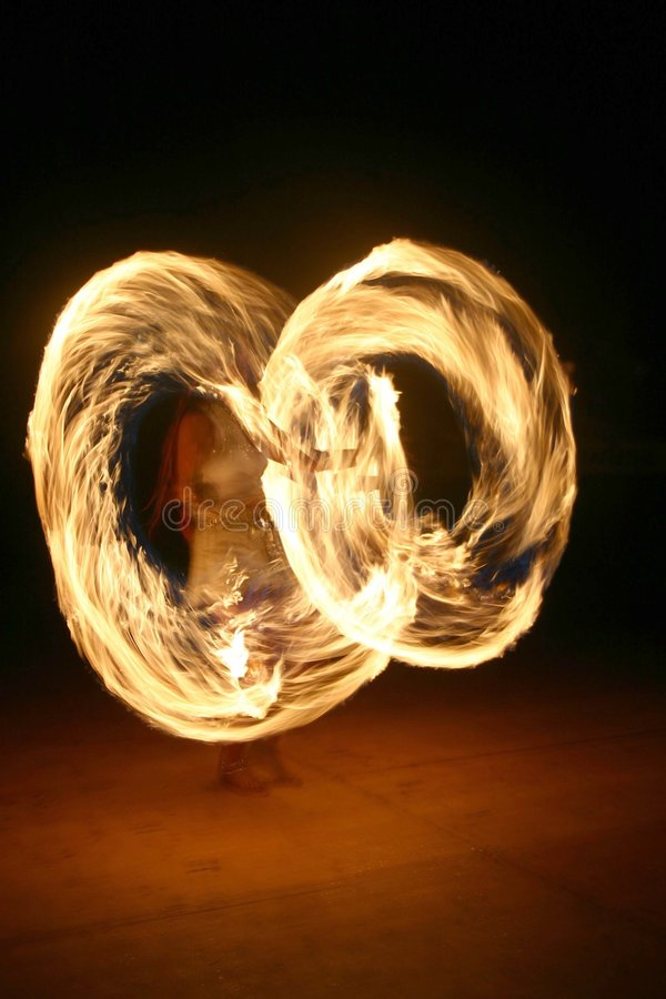Fire juggler. A young, attractive woman juggling with burning sticks stock image