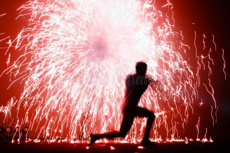 Fire juggler and sparks. A fire juggler - red background royalty free stock photo