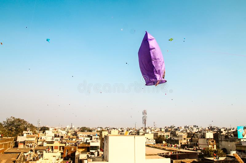 Fire kite flying over clear blue sky during traditional hindu kite festival in indian city stock images