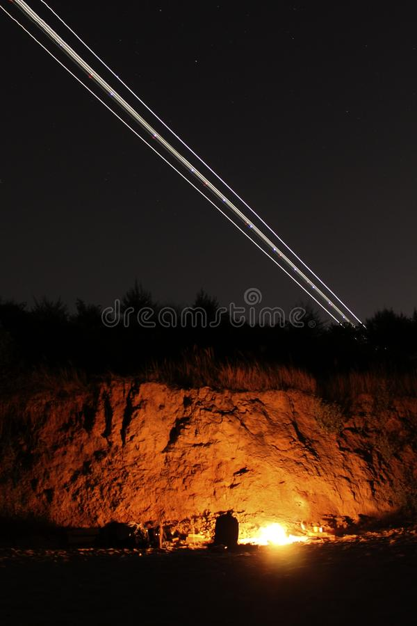 Fire-lit camping spot and airplane trail royalty free stock photos