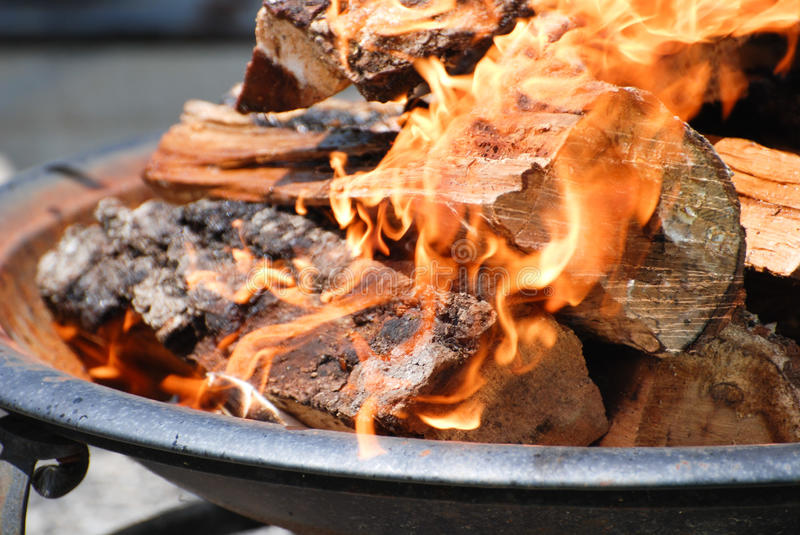 Fire. Logs burning in a round fire pit stock photos