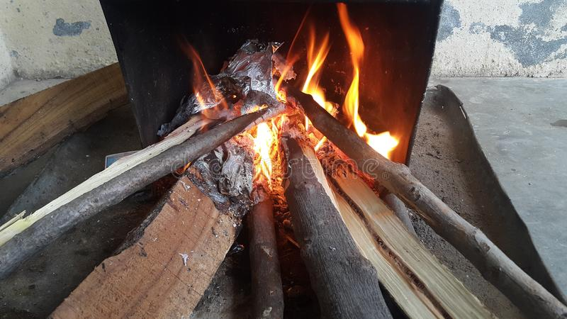 Fire on logs in fire pot with embers and burning coal and blazing flames royalty free stock photography