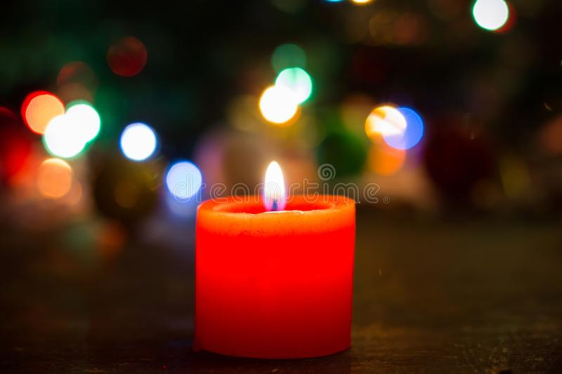 Fire of lonely red candle on christmas background stock photography