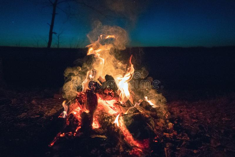 Fire at night against the dark sky. stock photos