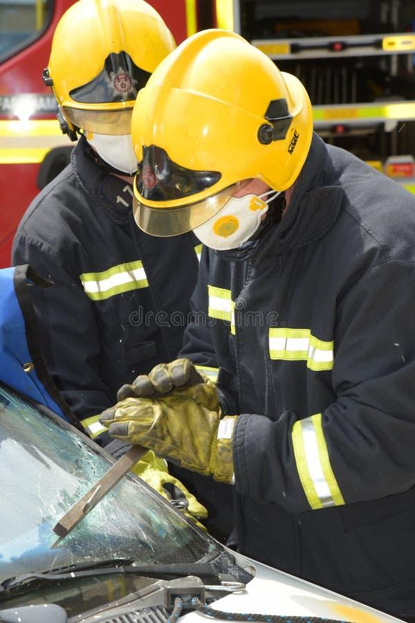 Fire officer cutting away a windscreen at car smash stock photos