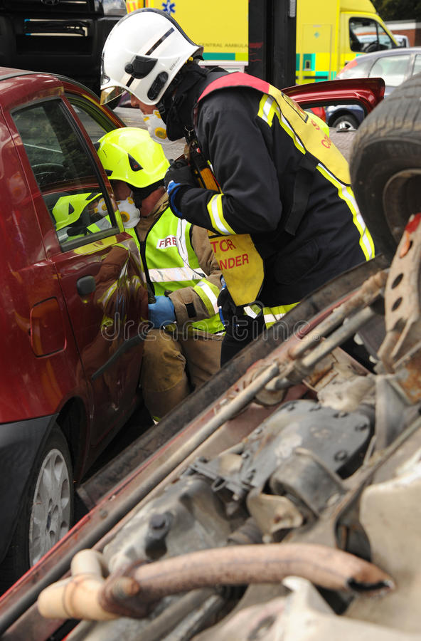 Fire officers at car crash. Fire service officers at the scene of a car car exercise Suitable for emergency service and insurance industry use royalty free stock photography