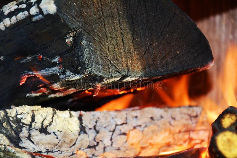 Fire and oven. Wood dark hard logs burning, orange flames and hot temperature royalty free stock photo