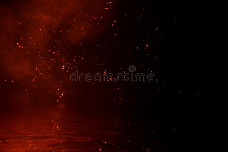 Fire particles embers with reflection in water. Design texture for banner,flyer,card. And poster stock image
