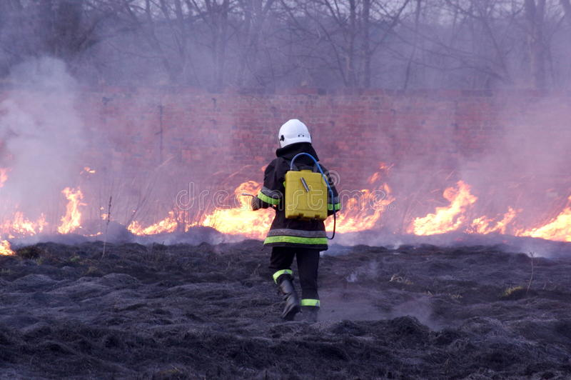 Fire. The photo shows a fire. We see the burning dry grass and firefighters carrying fire-fighting. Above the ground rises smoke royalty free stock photos