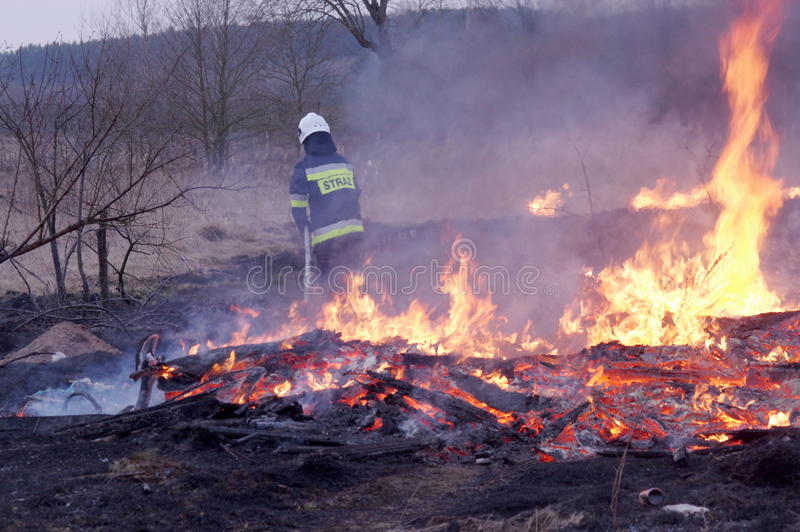 Fire. The photo shows a fire. We see the burning dry grass and firefighters carrying fire-fighting. Above the ground rises smoke stock photos