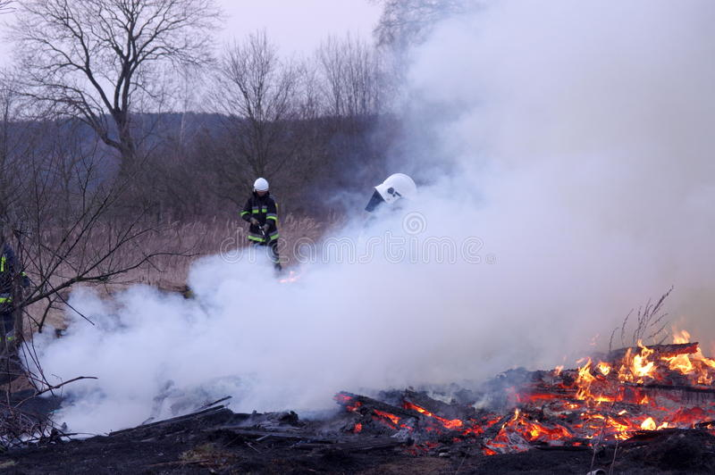 Fire. The photo shows a fire. We see the burning dry grass and firefighters carrying fire-fighting. Above the ground rises smoke stock photo
