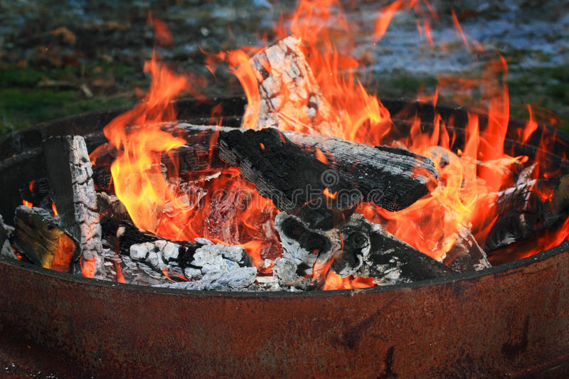 Fire Pit. A fire of cut wood and sticks in a round burn barrel. Shallow depth of field royalty free stock images
