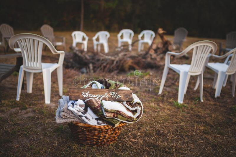 A Fire Pit With Plastic Chairs Around It And A Basket Of Blankets.