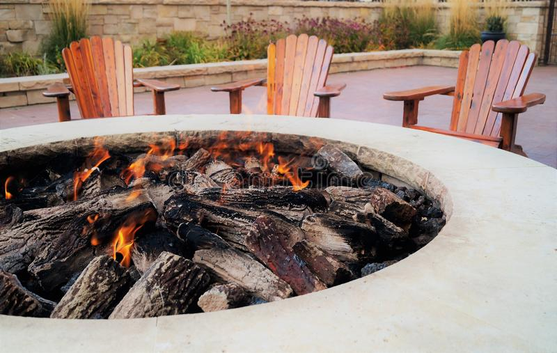 Fire pit with flames. Adirondack chairs by the fire pit stock photos