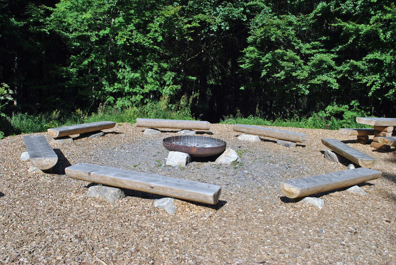 Fire pit. A fire pit in the forest with some benches stock photos