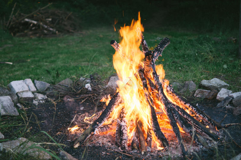 Fire pit. Nice coloured burning fire in the fire pit, stones and green grass around stock photography