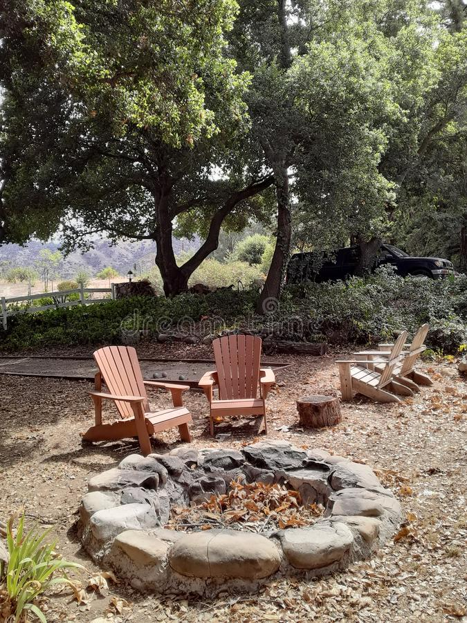 Fire Pit with Outdoor Furniture under Oak Trees with Bocce Ball Court royalty free stock photo