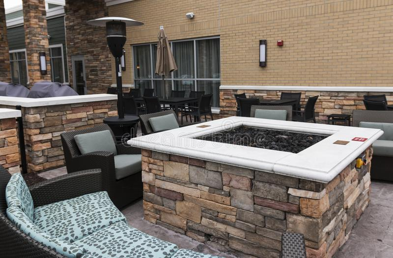 Fire pit outside of a hotel. A relaxing area is set up outside of an upstate new york hotel that has a fire pit, couches, chairs and a heat lamp royalty free stock images