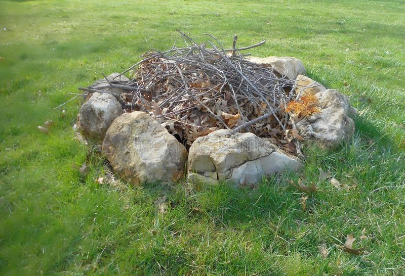 Fire pit ready to be lit. Fire pit full of twigs, leaves, and branches stock photos