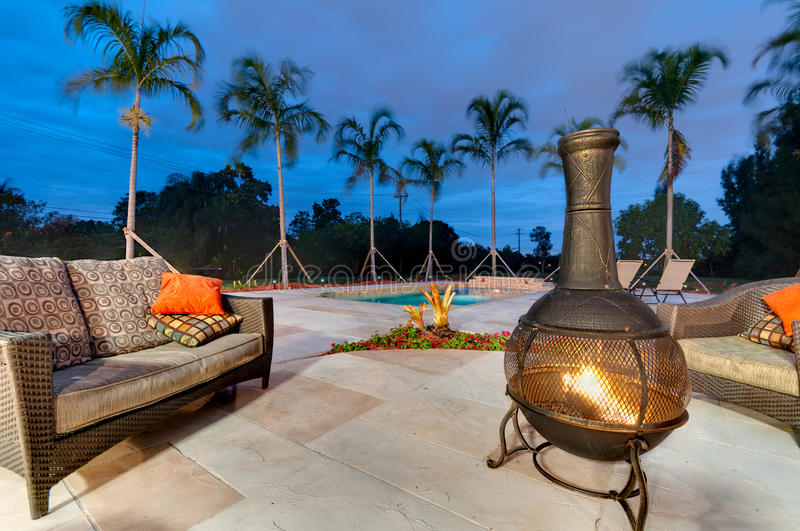 Fire pit and swimming pool. Fire pit in a patio at dusk with swimming pool and palms stock photography